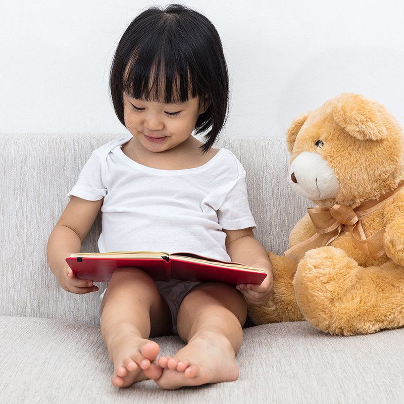 Little girl reading a book with her bear