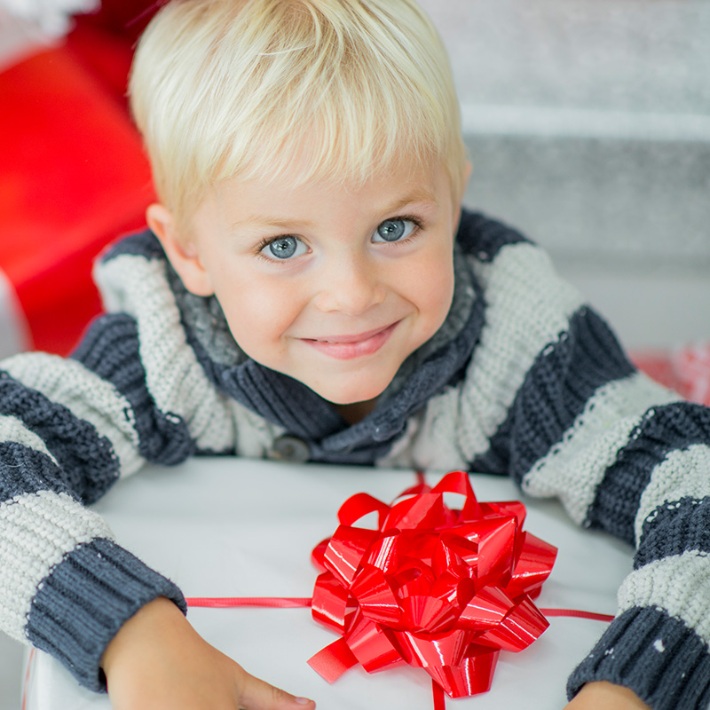Little boy opening his present smiling